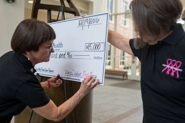 Survivors for Research presenting their yearly donation to Dr. Jonothan Licht, Director of the Cancer Center, and a group of breast cancer researchers.