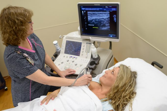 A practitioner performs an ultrasound on a breast cancer patient