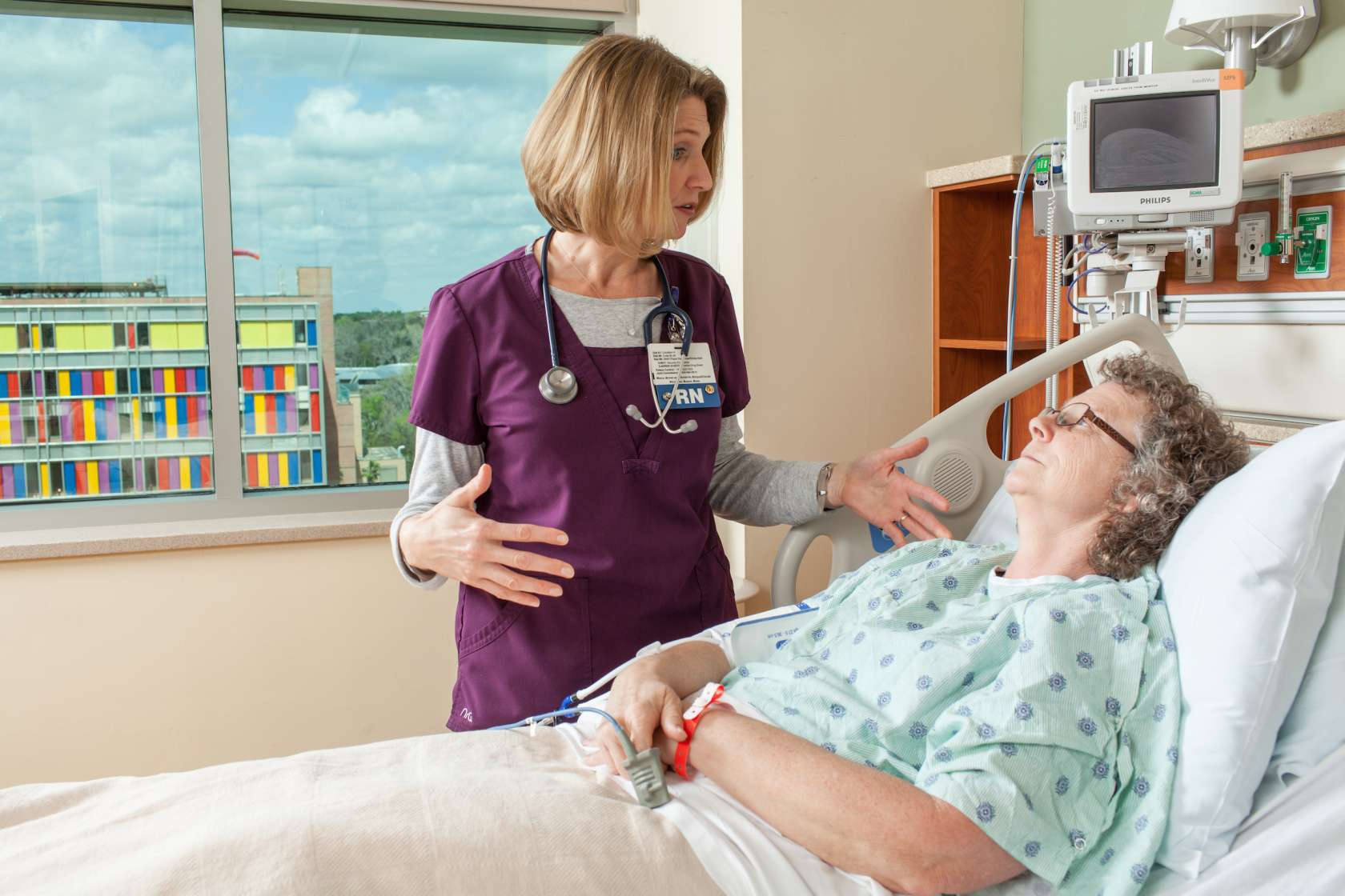 A nurse talks with a patient in the hospital